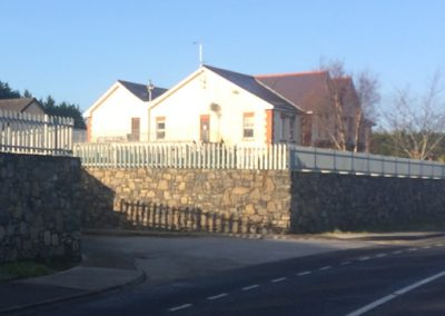 Stone wall with fencing above around house